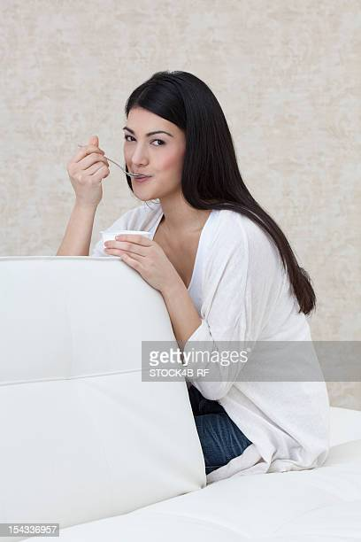 Dark-haired young woman eating yogurt