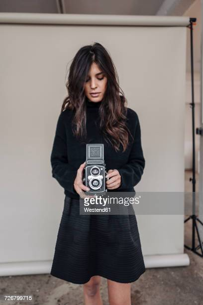 dark-haired young woman holding vintage camera in studio - black skirt stock pictures, royalty-free photos & images