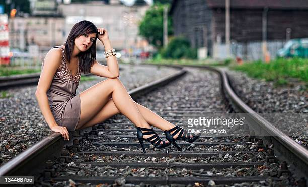 Dark-haired young woman wearing a beige dress and high heels posing while sitting on a railway track