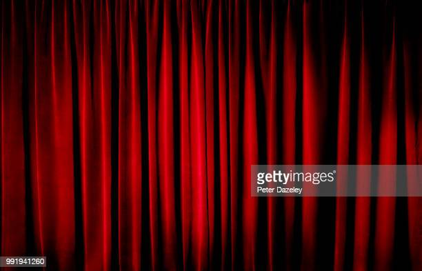 darkly lit theatre curtains - arts culture and entertainment stock pictures, royalty-free photos & images