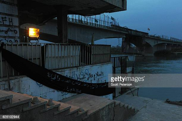Darkness gathers over the memorial to the Islamic State massacre of 1700 Shiite Air Force cadets from Camp Speicher beneath a bridge where victims...