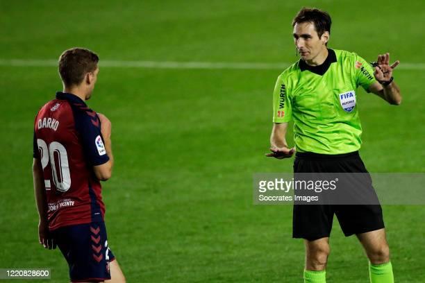 Darko Brasanac of CA Osasuna referee Ricardo de Burgos Bengoetxea during the La Liga Santander match between Osasuna v Atletico Madrid at the El...