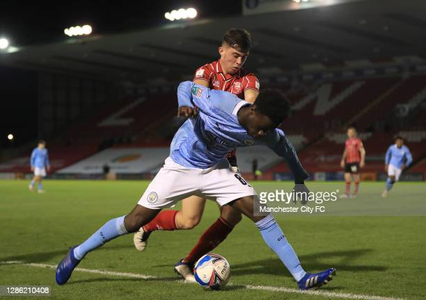 Darko Gyabi of Manchester City U21 holds off Sean Roughan of Lincoln City during the EFL Trophy match between Lincoln City and Manchester City U21 at...