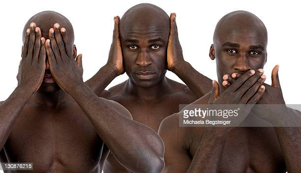 Dark-skinned man, not wanting to see, hear and say, three wise monkeys