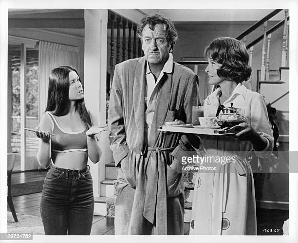 Darleen Carr and Lola Albright looking at shell shocked David Niven in a scene from the film 'The Impossible Years' 1968