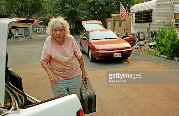 Darlene Bruce stares at the smoky hillside as she packs belongings in her car at the small community of Camp Williams near the San Gabriel River as...