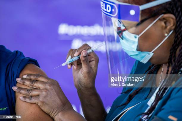 Darlene Dickens-Jeffers, right, senior manager of infection prevention at AltaMed Health Services, gives a Moderna COVID-19 vaccination to former Los...
