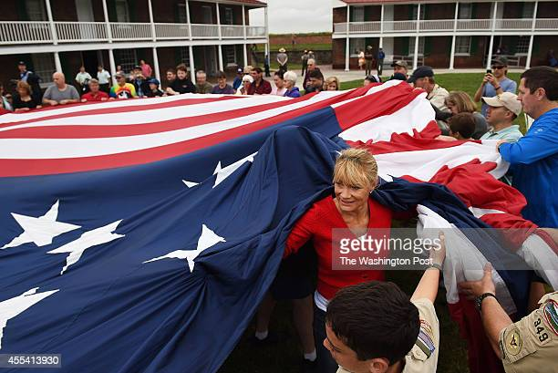 Darlene McGinnis of Virginia Beach VA right helps to hold up a large American flag during a changing of the flag event dring the StarSpangled...