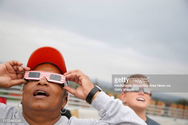 Darlene Pogue left and Anthony Pulido right watch a solar eclipse from the roof of a parking garage at Ohlone College on Monday Aug 21 in Fremont...
