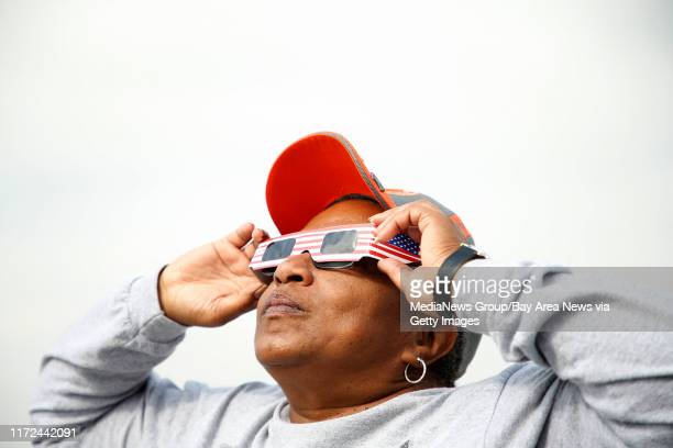 Darlene Pogue watches a solar eclipse from the roof of a parking garage at Ohlone College on Monday Aug 21 in Fremont Calif