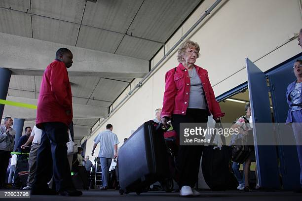 Darlene Renfro from Fort Worth Texas pulls her luggage behind her after disembarking from the Carnival Liberty Cruise ship at Port Everglades on...