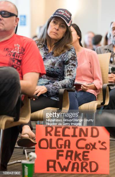 Darlene Savord center of Tustin listens to speakers during open comments at the Coast Community College District board of trustee meeting in Costa...