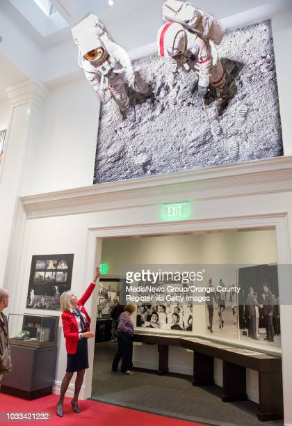Darlene Sky left a docent at The Richard Nixon Presidential Library Museum points out a large display hanging from the wall of the 1969 moon walk in...
