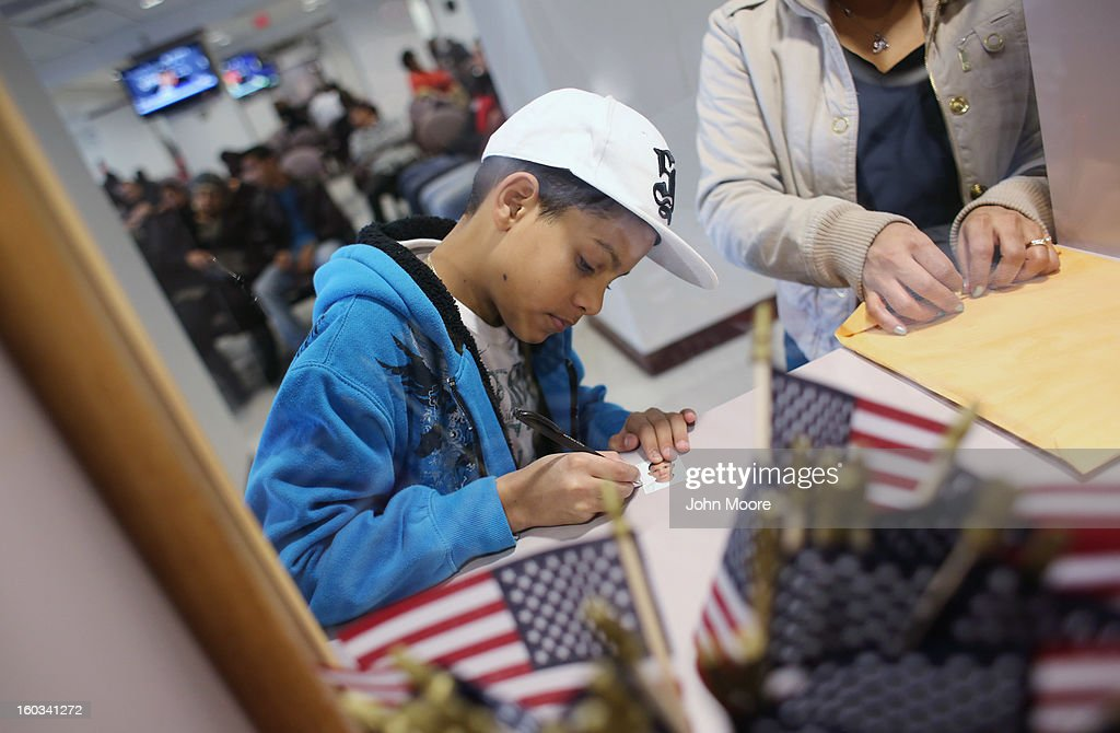 Darlin Gonzalez, 10, whos family immigrated from the Dominican Republic, signs a passport photo at the U.S. Citizenship and Immigration Services (USCIS), district office on January 29, 2013 in New York City. Some 118,000 immigrants applied for U.S. citizenship and 2,500 children received citizenship certificates in the New York City dictrict in 2012. Although underage children of naturalized immigrants usually receive U.S. citizenship, they must go through a process at the USCIS in order to receive legal certificates. Children born in the United States are American, regardless of the immigrant status of their parents.