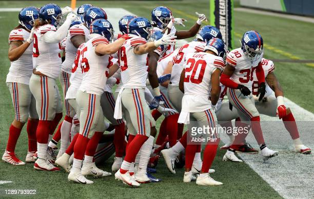 Darnay Holmes of the New York Giants celebrates with his teammates after intercepting a pass thrown by Russell Wilson of the Seattle Seahawks during...