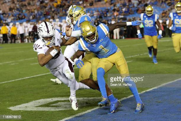 Darnay Holmes of the UCLA Bruins is unable to keep Jayden Daniels of the Arizona State Sun Devils from scoring a rushing touchdown during the second...