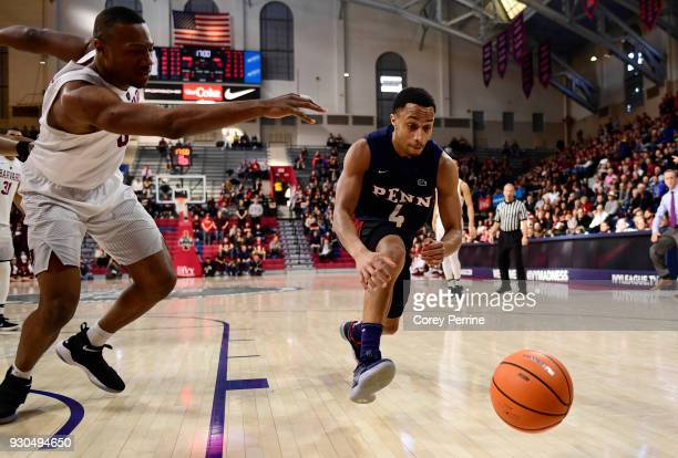 Darnell Foreman of the Pennsylvania Quakers and Chris Lewis of the Harvard Crimson eye the ball during the first half of the Men's Ivy League...