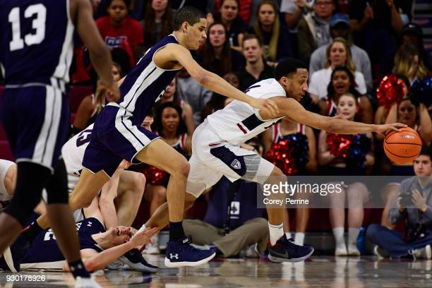 Darnell Foreman of the Pennsylvania Quakers and Paul Atkinson chase down a ball as Blake Reynolds of the Yale Bulldogs lays on his back during the...