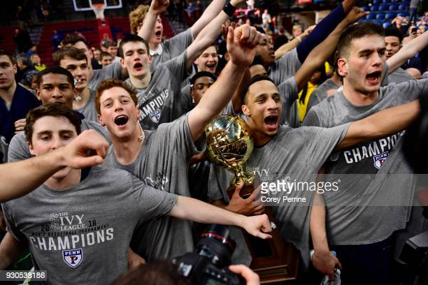 Darnell Foreman of the Pennsylvania Quakers holds the championship trophy as he and the team perform the traditional Penn fight song after winning...