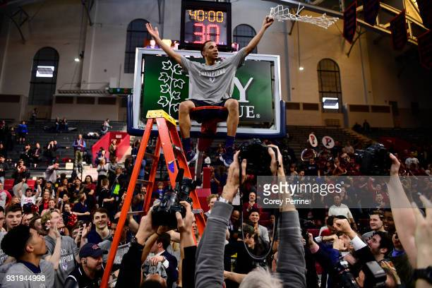 Darnell Foreman of the Pennsylvania Quakers sits atop the rim after the win at The Palestra on March 11, 2018 in Philadelphia, Pennsylvania. Penn...