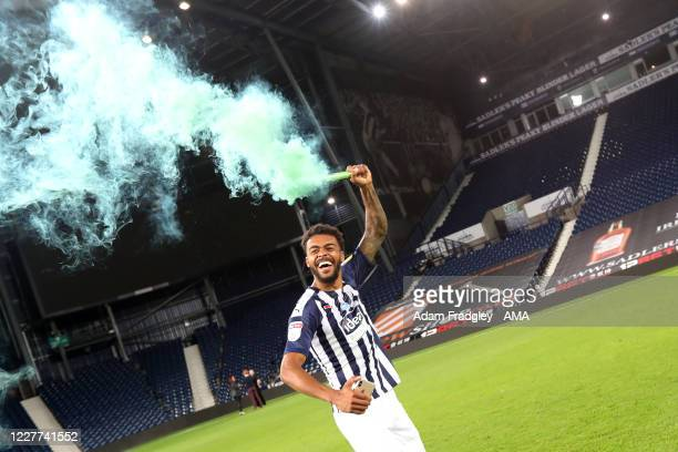 Darnell Furlong of West Bromwich Albion celebrates promotion to the Premier League on the pitch at the end of the Sky Bet Championship match between...