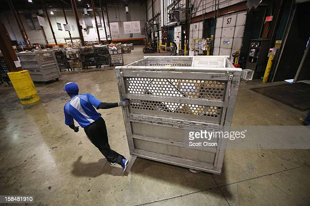 Darnell Horton unloads mail from a truck at the United States Postal Service Chicago Logistics and Distribution Center on December 17 2012 in Elk...