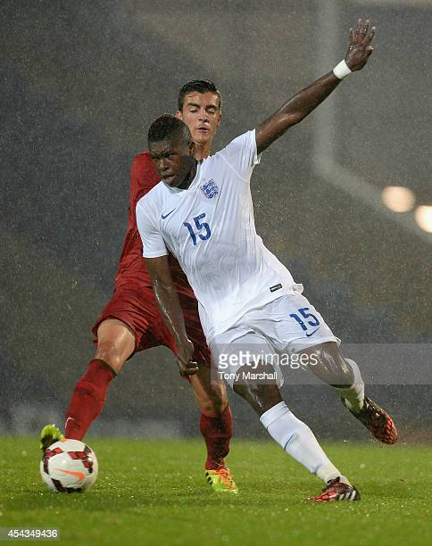 Darnell Johnson of England is tackled by Marcelo of Portugal during the Under 17 International match between England U17 and Portugal U17 at Proact...