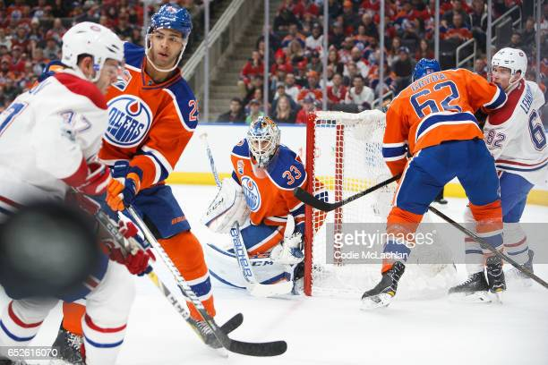 Darnell Nurse and goalie Cam Talbot of the Edmonton Oilers keep their eyes on the puck as Alexander Radulov of the Montreal Canadiens looks for the...