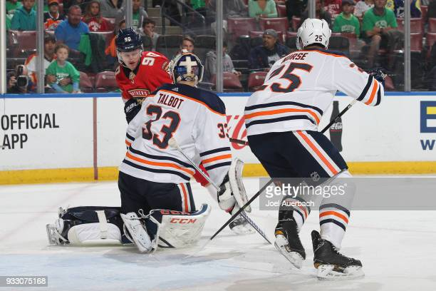 Darnell Nurse looks on as goaltender Cam Talbot of the Edmonton Oilers stops a shot by Jared McCann of the Florida Panthers during first period...