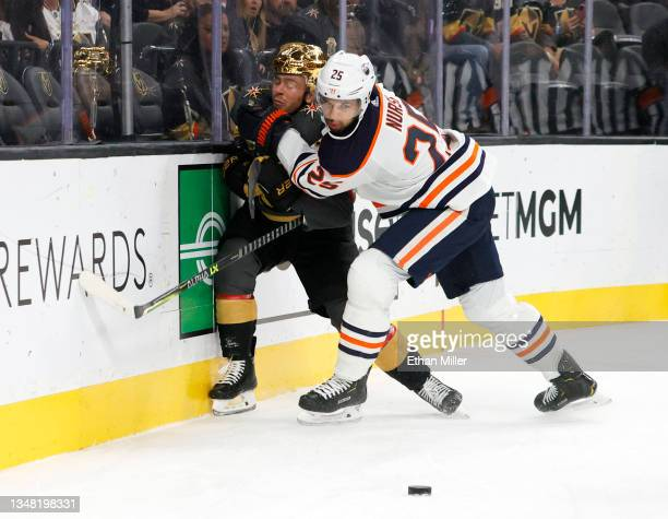 Darnell Nurse of the Edmonton Oilers checks Jonathan Marchessault of the Vegas Golden Knights into the boards in the second period of their game at...
