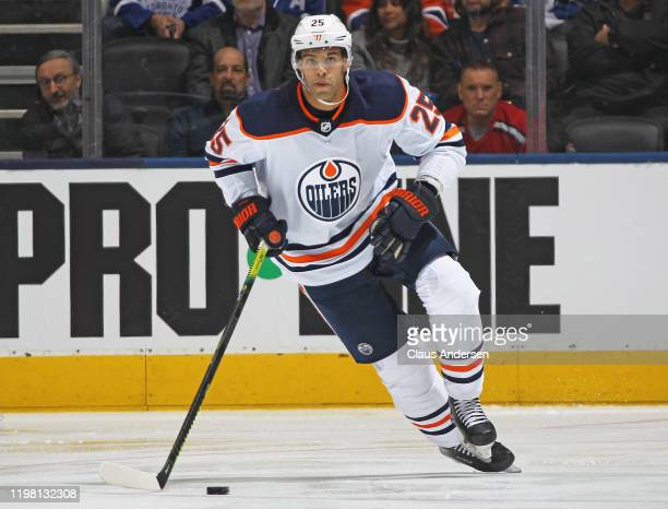 Darnell Nurse of the Edmonton Oilers heads up ice with the puck against the Toronto Maple Leafs during an NHL game at Scotiabank Arena on January 6...