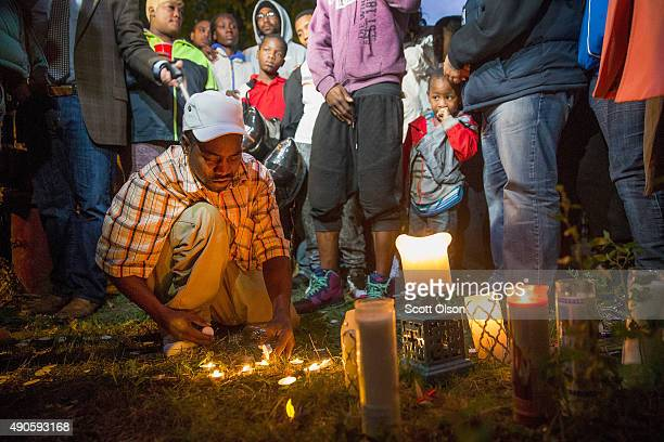 Darnell Wells lights a candle to remember 24yearold niece Patricia Chew and her 46yearold mother his sister Lolita Wells at a memorial service where...