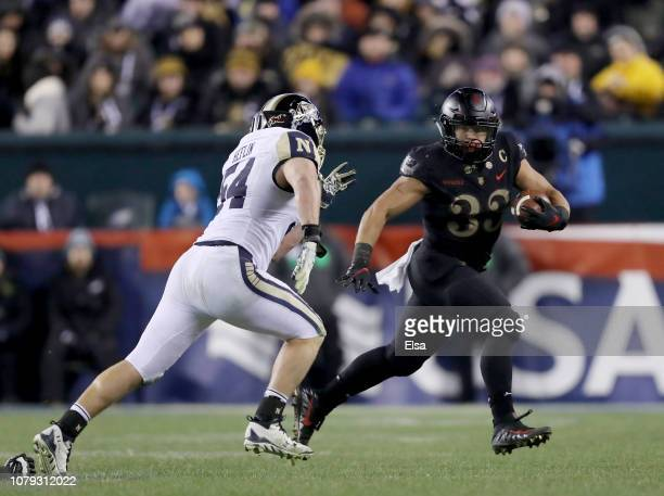 Darnell Woolfolk of the Army Black Knights carries the ball as Taylor Heflin of the Navy Midshipmen defends at Lincoln Financial Field on December 08...