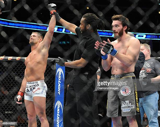 Daron Cruickshank has his hand raised in victory by referee Herb Dean after a lightweight bout during UFC on Fox 10 Henderson v Thomson at United...