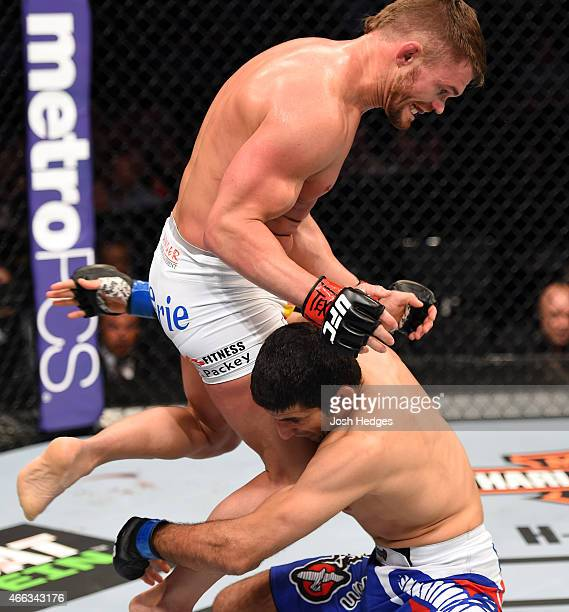 Daron Cruickshank lands a flying knee to the body of Beneil Dariush in their lightweight bout during the UFC 185 event at the American Airlines...