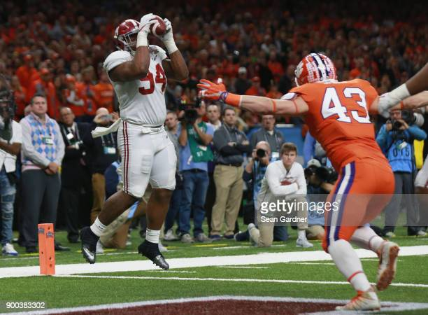 Da'Ron Payne of the Alabama Crimson Tide catches the ball for a touchdown as Chad Smith of the Clemson Tigers defends in the second half of the...