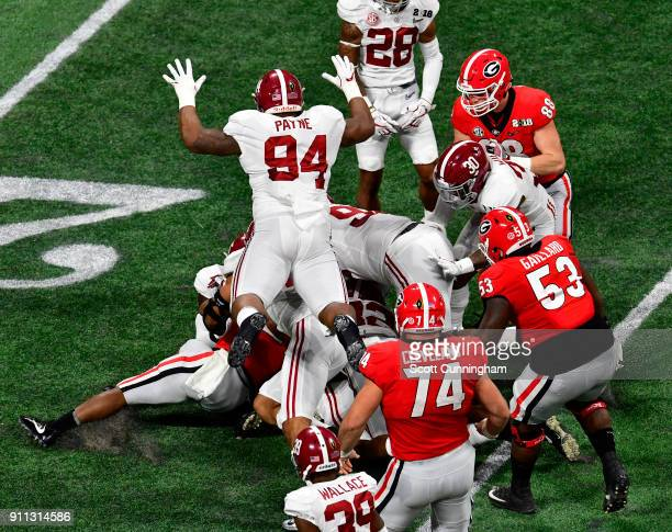 Da'Ron Payne of the Alabama Crimson Tide finishes a tackle against Sony Michel of the Georgia Bulldogs in the CFP National Championship presented by...