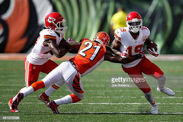 Darqueze Dennard of the Cincinnati Bengals attempts to tackle Jeremy Maclin of the Kansas City Chiefs while being blocked by Chris Conley of the...
