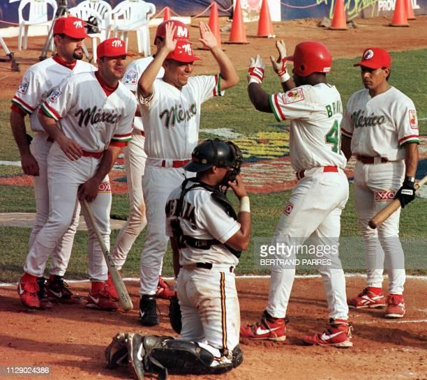 Darrel Brinkley de Mexico es saludado por sus companeros de equipo delante del catcher de Puerto Rico Ben Molina luego de batear un honron en el...