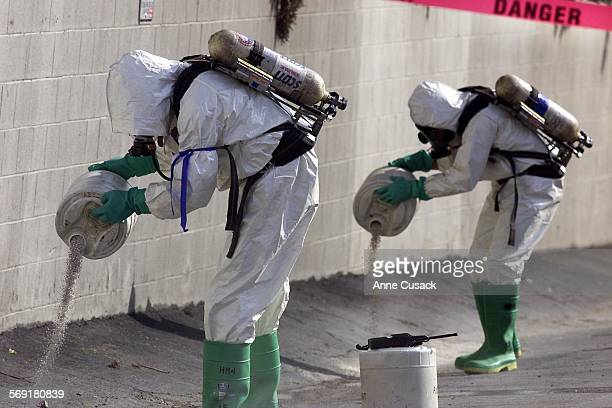 Darrel Sandford right and Robert Wilson left members of the Federal Fire Department Hazardous Materials Ventura County Group pour a neutral absorbent...
