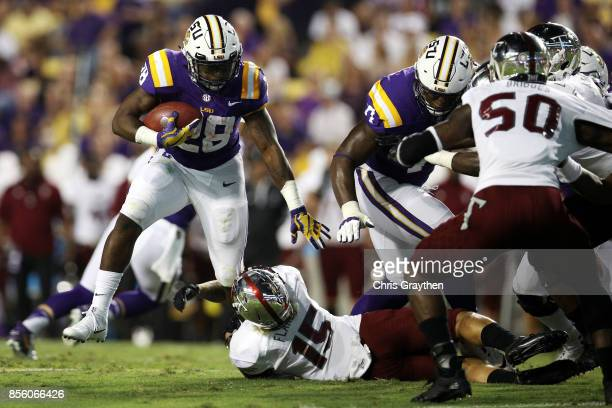 Darrel Williams of the LSU Tigers is tackled by Andre Flakes of the Troy Trojans at Tiger Stadium on September 30 2017 in Baton Rouge Louisiana
