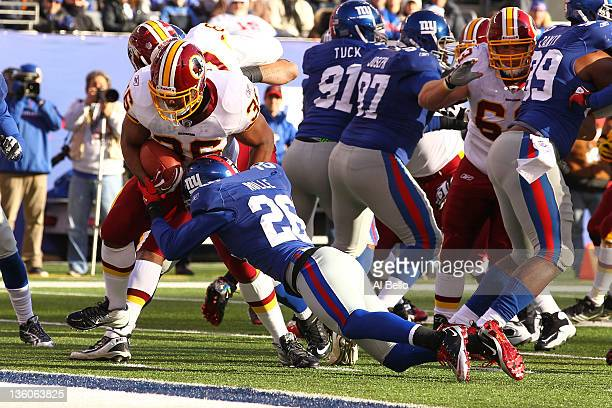Darrel Young of the Washington Redskins scores a touchdown as Antrel Rolle of the New York Giants misses the tackle during their game at MetLife...