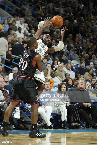 Darrell Armstrong of the New Orleans Hornets looks to pass as he is covered by Eric Snow of the Philadelphia 76ers during the game at the New Orleans...
