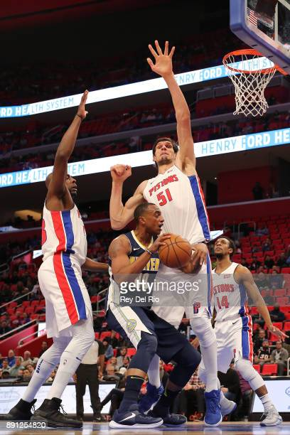 Darrell Arthur of the Denver Nuggets drive to the basket against Boban Marjanovic of the Detroit Pistons at Little Caesars Arena on December 12 2017...