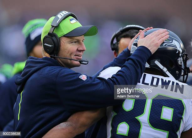 Darrell Bevell congratulates Doug Baldwin of the Seattle Seahawks after scoring a touchdown in the fourth quarter on December 6, 2015 at TCF Bank...