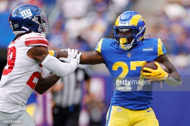 Darrell Henderson of the Los Angeles Rams carries the ball as Xavier McKinney of the New York Giants defends during the first half at MetLife Stadium...