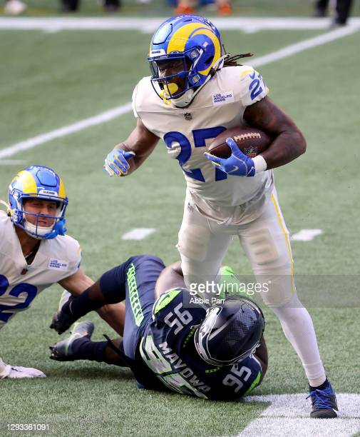 Darrell Henderson of the Los Angeles Rams is tackled by Benson Mayowa of the Seattle Seahawks during the first quarter at Lumen Field on December 27,...