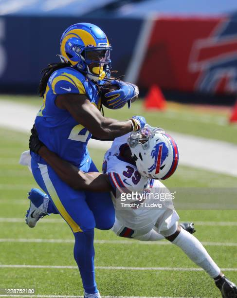Darrell Henderson of the Los Angeles Rams runs the ball as Levi Wallace of the Buffalo Bills tries to make the tackle during the first half at Bills...