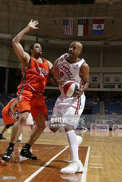 Darrell Johns of the Fayetteville Patriots drives against Kevin Lyde of the Columbus Riverdragons December 12, 2003 at the Crown Coliseum in...
