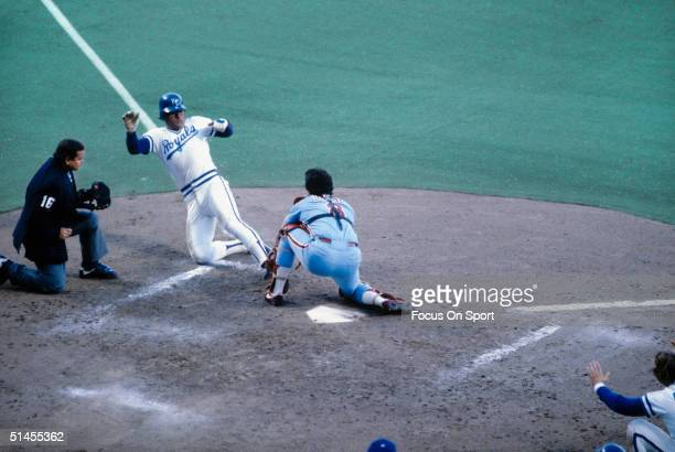 Darrell Porter of the Kansas City Royals slides into home plate guarded by Bob Boone of the Philadelphia Phillies during the World Series at Royals...